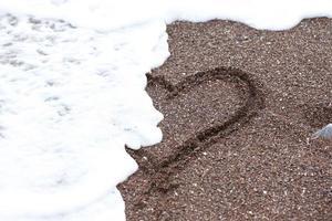 cuore disegnato nella sabbia che viene cancellato da un'onda foto