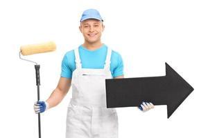 giovane decoratore in uniforme bianca che tiene un rullo di vernice foto