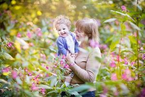 bella donna che gioca con una bambina che ride sul tramonto foto