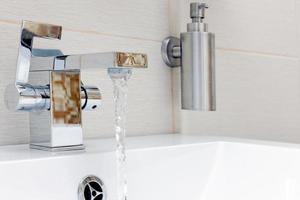 rubinetto cromato con acqua. foto
