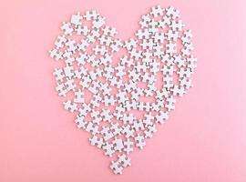 puzzle fatto cuore tagliente su sfondo rosa foto