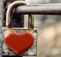 lucchetto a forma di cuore arrugginito invecchiato bloccato sulla ringhiera metallica foto