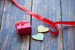 due cuori modellano giocattoli e regali su fondo in legno. foto