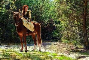 donna guerriera armata di arco a cavallo foto