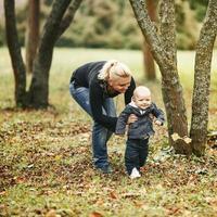felice giovane mamma con bel figlio nel parco in autunno.