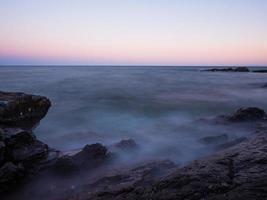 onde che si infrangono sulla riva del lago superiore al tramonto