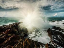 onda dell'oceano liscia con sfondo di formazione rocciosa