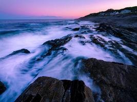 onda dell'oceano liscia con sfondo di formazione rocciosa foto