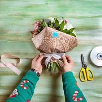 fiorista che fa bouquet di fiori su un tavolo foto