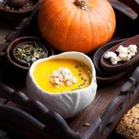 zuppa di zucca con popcorn salato in una ciotola di ceramica bianca foto