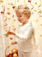 dolce angelo ragazzo con coriandoli di stelle d'oro foto