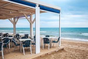 bar interno lato mare con pavimento in legno e poltrone in metallo