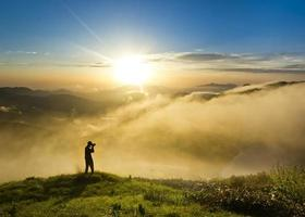 uomo su una collina al tramonto con la fotocamera che fa foto