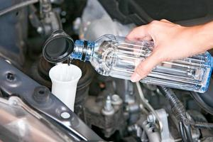 riempire il liquido dell'acqua del parabrezza su un'auto.