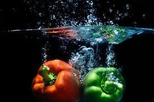 peperone dolce cadere in acqua su sfondo nero.
