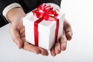confezione regalo bianca con nastro rosso in mano foto