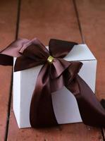 confezione regalo bianca con fiocco in nastro su uno sfondo di legno