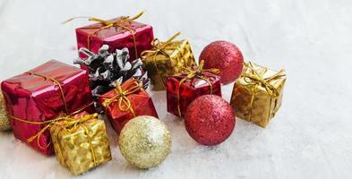 regali di natale dorati e rossi e palline nella neve