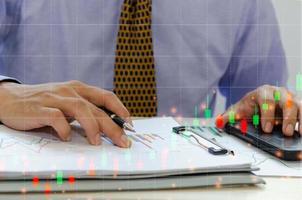 uomo d'affari tenendo la penna, controllando i grafici