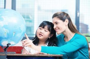 insegnante di scuola elementare che spiega il globo terrestre alla femmina asiatica