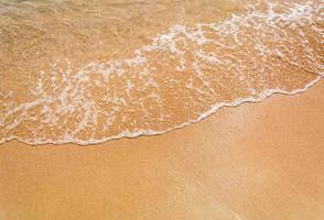 le onde del mare rotolano sulla sabbia gialla e fine