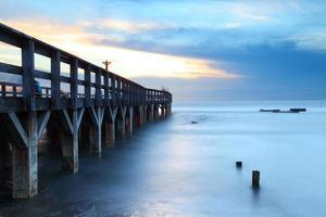 ponte di legno in mare al tramonto foto