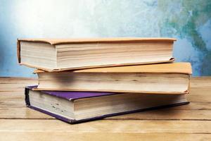 tre vecchi libri sulla tavola di legno foto