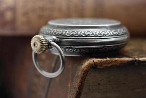 orologio d'argento e libri antichi foto