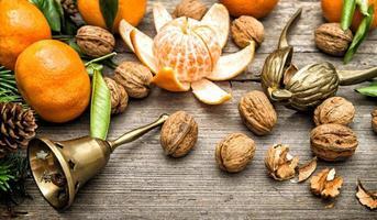 frutti di mandarino, noci e rami di alberi di Natale
