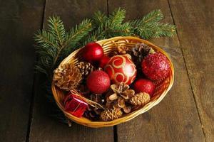 decorazioni natalizie in cesto e rami di abete rosso su fondo in legno