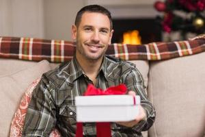 uomo sorridente che offre un regalo il giorno di Natale