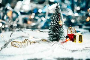 albero di natale in miniatura, pupazzo di neve e regali sulla neve foto