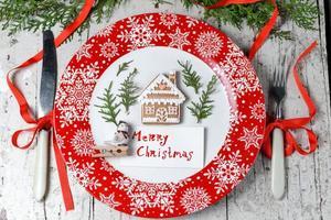 decorazioni natalizie per la tavola con piatto rosso e posate foto