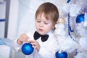 ragazzo in camicia e cravatta decora un albero di Natale