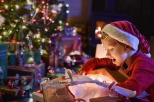 Natale, ragazzino che apre un regalo vicino all'albero illuminato