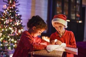 Natale, 2 bambini che aprono un regalo vicino all'albero illuminato