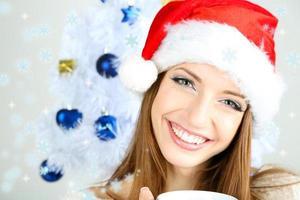 bella ragazza sorridente vicino all'albero di Natale con la tazza foto