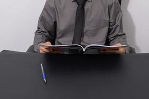 uomo d'affari che legge un libro alla sua scrivania