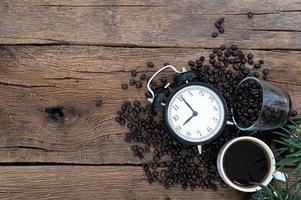 sveglia, una tazza di caffè e chicchi di caffè sulla scrivania