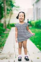 felice bambina asiatica in abito in piedi sul sentiero nel parco