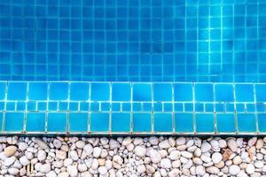fondo del modello delle mattonelle e riflesso dell'acqua nella piscina. foto