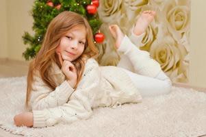 ragazza sdraiata sul tappeto vicino all'albero di natale.