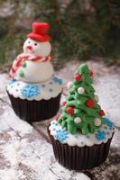 cupcake albero di natale su sfondo con pupazzo di neve foto