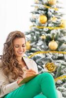sorridente giovane donna scrivendo in una cartolina vicino all'albero di Natale