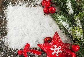 cartolina di Natale con neve, stella rossa e ramo di abete