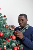 uomo che decora l'albero di Natale e che guarda l'obbiettivo