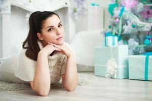 ragazza sdraiata vicino a un albero di natale bianco con doni
