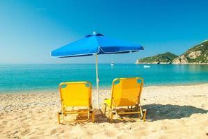 Lettini e ombrelloni sulla bellissima spiaggia, l'isola di Corfù, Grecia foto
