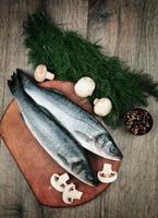 branzino crudo di pesce sulla tavola di legno foto