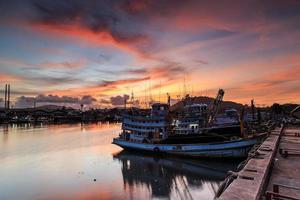 barca da pesca stand al molo e bel tramonto a phuket